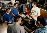 Students talking with each other while working on a machine with the professor observing at Mankato State University