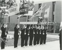 Nine young women as flag guards in front of Memorial Library.