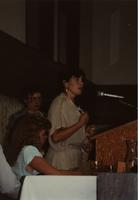 School of Nursing Pinning Ceremony at the Holiday Inn, Mankato, 1990-92. Seated: Lindy Olsen; Standing: Dr. Kathryn Schweer (back), Patricia Cretelli (podium).