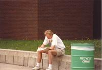 A student sits near the Memorial Library and reads The Reporter at Mankato State University, 1991-05.