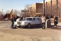 Students surrounds a white vehicle on the Campus Mall at Mankato State University, 1989-01-24.