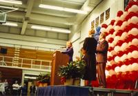 Hillary Clinton stands behind a podium and gives a speech in Otto Arena at Mankato State University, 1992-10.