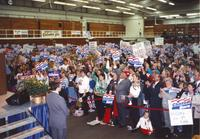Crowd enthusiastically cheers on speaker behind podium at the Clinton-Gore campaign in Otto Arena at Mankato State University, 1992-10.