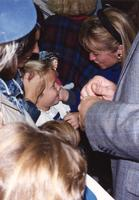 Hillary Clinton embraces and talks to a child at the Clinton-Gore campaign at Otto Arena at Mankato State University, 1992-10.