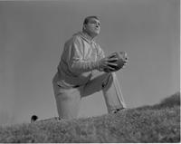 Coach kneeling and holding football, Mankato State College, January 13, 1961