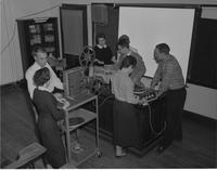 Several professors help set up film materials at Mankato State College, 1957-09-19.