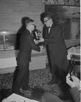 A man presents a plaque to a colleague at Mankato State University, 1959-08-09.