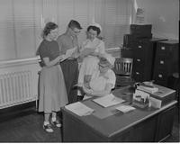 Two nurses share information with one another, Mankato State College March 31, 1958. A602