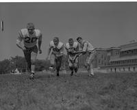 Action shot of four players at practice Mankato State College September 14, 1961.