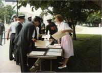 Woman handing out certificates at ROTC ceremony; Mankato State University