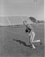 Bernie Maczuca poses while running with a football at Blakeslee Stadium at Mankato State College, 1968-10-01.