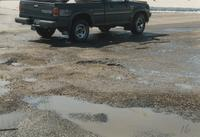 A picture of a small truck driving near potholes in Stadium Road near Mankato State University, 1989.