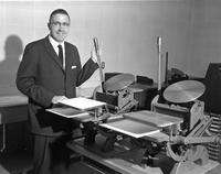 An administrator with a letterpress printing machine, Mankato State College, 1960-10-31