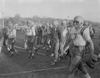 Football players walk off field after a game at Mankato State College, 1958-11-11.