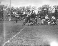 Action shot of Mankato State College football team against opponent, 1958-12-02.