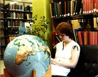 Student studies in the library by the world globe, Mankato State University date presumed to be 1990s.