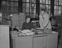 Benjamin A. Buck is talking to a secretary at a office in Mankato State College, 1958-04-02.