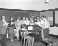 Students are singing next to the piano at Mankato State College, 12-08-1958.