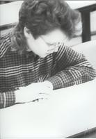 Female student taking a test in a lecture hall at Mankato State University.
