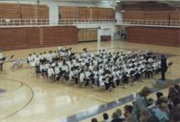 The Mankato State University band seated in front of an audience in Otto Recreation Center for an event, 1980s.
