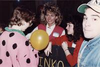 A group of four people standing, some holding a sign and a balloon, during an event at Mankato State University, 1980s.