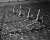 Dolphin swimmer floats with their legs in the air at Mankato State College, 1959-03-10.