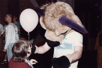 A Maverick mascot gives a balloon to an eventer in the Centennial Student Union at Mankato State University, 1980s.