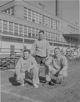 Three unknown male students playing baseball on the field, Mankato State College, 1959-03-18