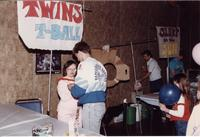 A man helping a woman at a carnival event at Mankato State University in the Centennial Student Union Ballroom, 1980s.