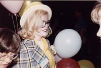 A blond girl with a painted clown face stands holding balloons during an event at Mankato State University, 1980s.