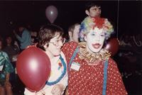 A clown puts his arm around an attendee at an event in the Centennial Student Union Ballroom at Mankato State University, 1980s.