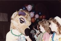 A Maverick mascot talks with two ladies, while someone in the background holds a handful of balloons during an event in the Centennial Student Union Ballroom at Mankato State University, 1980s.