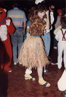 A girl in a hula costume dances among a group of people at an event in the Centennial Student Union Ballroom at Mankato State University, 1980s.