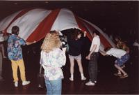 A group of people playing a game with a parachute in the Centennial Student Union Ballroom during an event at Mankato State University, 1980s.