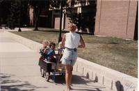 Woman pushing stroller with children through the Campus Mall, Mankato State University, 1989.