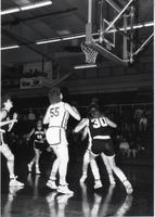 Players looking up to see the ball and get in position for a possible rebound during a game at Mankato State University