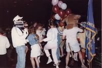 A group of people, including a Maverick mascot, dance while being videotaped during an event at Mankato State University, 1980s.