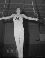 Gymnastics athlete, George Dallage, on the rings at Mankato State College, 1960-02-24.