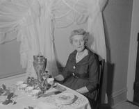 Marie Bruce sits elegantly at a buffet table, Mankato State College, 1960-02-24.