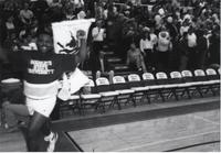 Maverick fan running around the court with Mavericks flag before a basketball game at Mankato State University