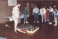 Group of adults playing a bottle game at an event in the Centennial Student Union Ballroom at Mankato State University, 1980s.