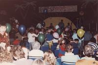 People can be seen sitting and dancing in front of a stage during an event at Mankato State University, 1980s.