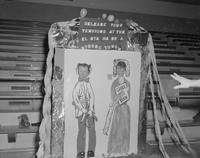Two staff stands behind photo booth and poses playfully at Mankato State College, 1960-03-29.