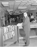 A male librarian looking over books, Mankato State College, August 22,1960