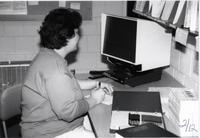 Worker writing information down while looking at a microfiche reader in the library at Mankato State University