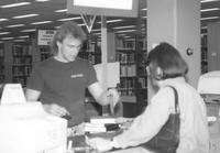 Library worker assists a patron in checking out books in Memorial Library at Mankato State University