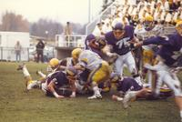 A group of football players tackle each other at a Minnesota State University football game against the Augustana Vikings at Blakeslee Stadium, 1987.
