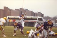 A group of Mankato State Football players run and tackle the players from the Augustana Vikings as number 43 kicks the football, at Blakeslee Stadium, 1987.