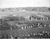 The Mankato State College marching band along with cheerleaders performing on the football field, April 25,1961. A3021
