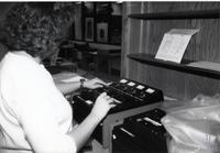 Worker putting cassette tapes onto a machine in the library at Mankato State University